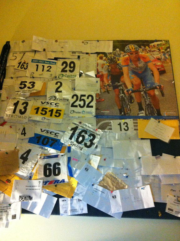 """Wiggo on the board above my bed. Been there for a few years now. Don't think that's even half of my race numbers either!"""