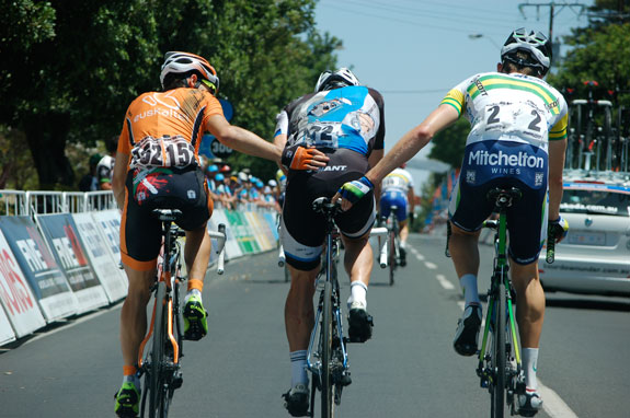 Durbridge (far right), in his first race at Australian champion, gives Graeme Brown and helping hand after a crash near the end of stage four of the Tour Down Under. Photo: Rob Arnold