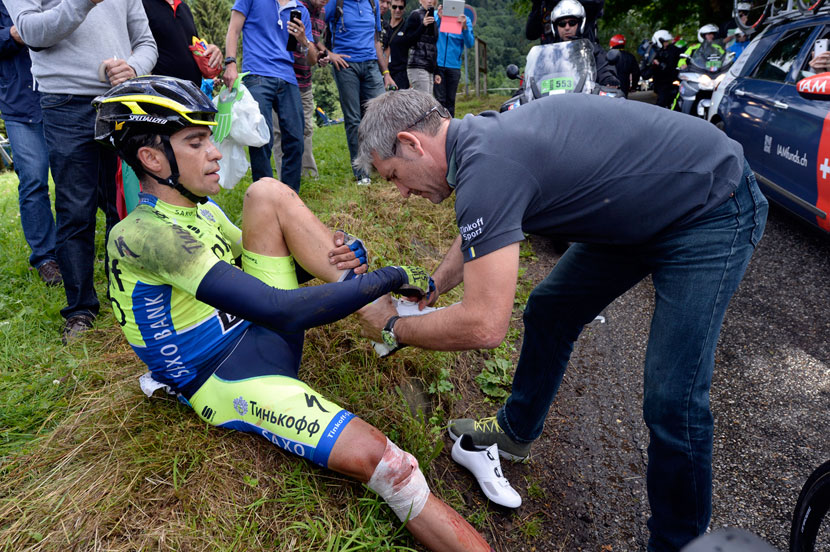 Alberto Contador gets a new set of shoes off his team's mechanic, Faustino Munoz, after being patched up by the Tour's medico... he would ride another four kilometres before quitting the race with a broken tibia. Photo: Graham Watson