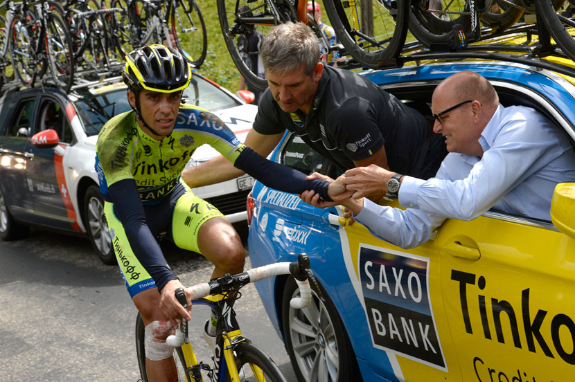 Contador is tended to by Faustino Munoz and Bjarne Riis as he rides along with a fractured tibia after his crash in stage 10 of the 2014 Tour. Photo: Graham Watson