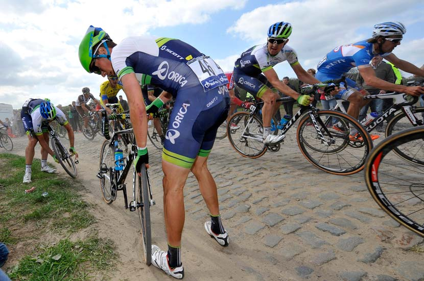 Paris-Roubaix, 2014. Luke Dubridge looks on as Jens Keukeleire swaps a flat front wheel with a team-mate after a puncture. Photo: Graham Watson